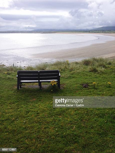 Empty Wooden Bench Towards Sea Against Cloudy Sky