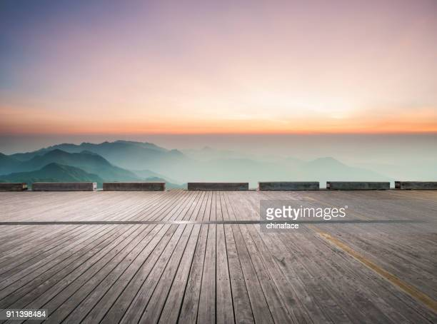 empty wooden board front of mountain ranges