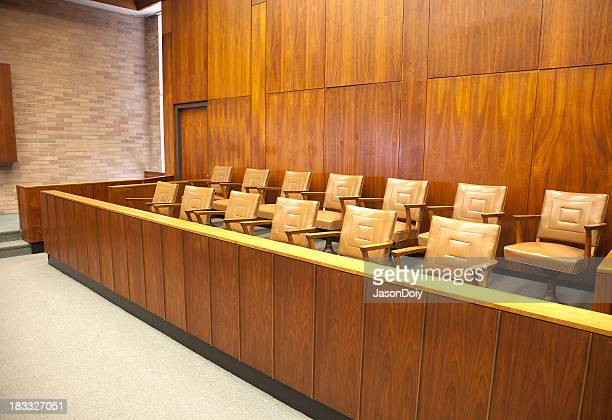 Empty wooden courtroom jury box with beige leather chairs