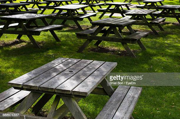 empty wooden picnic tables arranged on grassy field - picnic table stock pictures, royalty-free photos & images