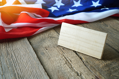 Empty wooden plate for your signature against the American flag. Copy space. 1255022006