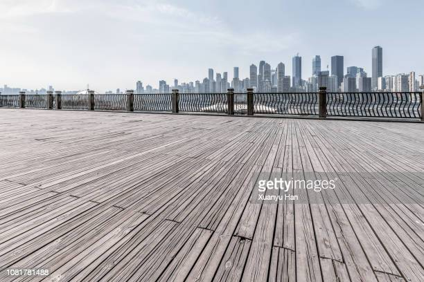 empty wooden platform with city skyline.