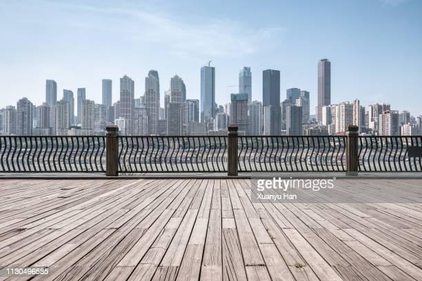 empty wooden platform with city skyline. - ウッドデッキ ストックフォトと画像