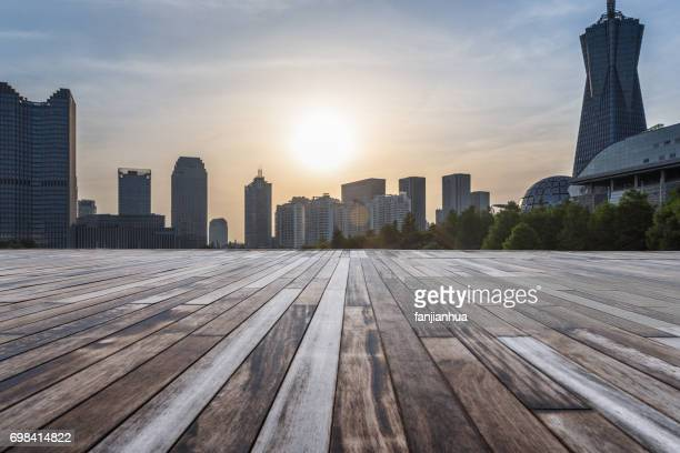 empty wooden platform with Shanghai skyline at dusk