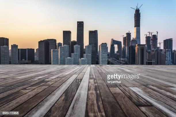 empty wooden platform with Shanghai skyline at dusk