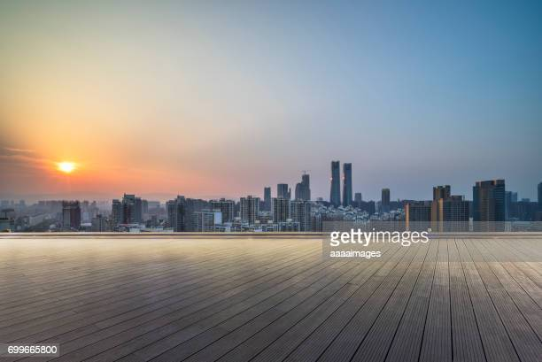 empty wooden platform with Suzhou skyline in background at dusk.