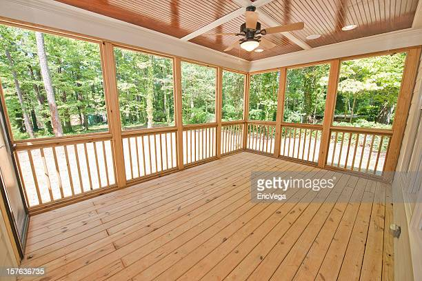 Empty, wooden rear patio with fan, lights and large windows