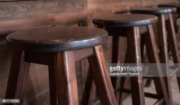 empty wooden stools in row at restaurant - stool stock pictures, royalty-free photos & images