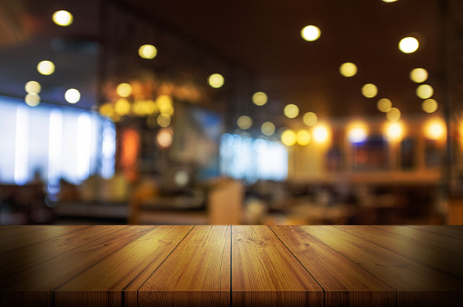 Empty wooden table top with blur coffee shop or restaurant interior background. 969671388