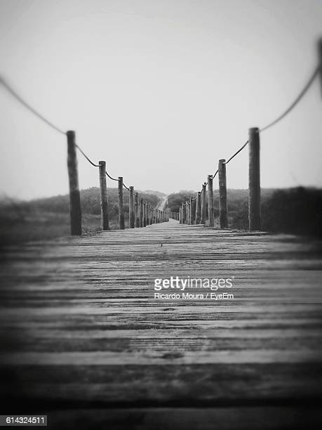 empty wooden walkway against sky - moura stock photos and pictures
