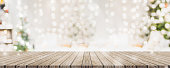 Empty woooden table top with abstract warm living room decor with christmas tree string light blur background with snow,Holiday backdrop,Mock up banner for display of advertise product.