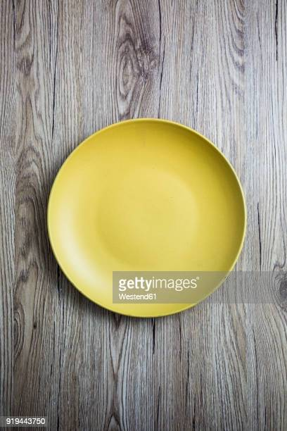 Empty yellow plate on wood