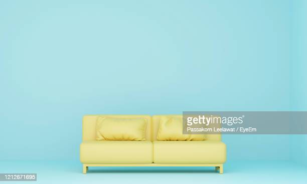 empty yellow seats against blue background - sofa stock pictures, royalty-free photos & images