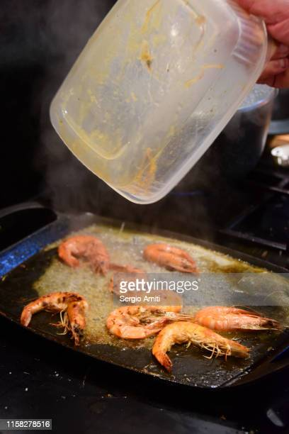emptying a plastic tub with shrimps onto a hot plate - plastic plate stock photos and pictures