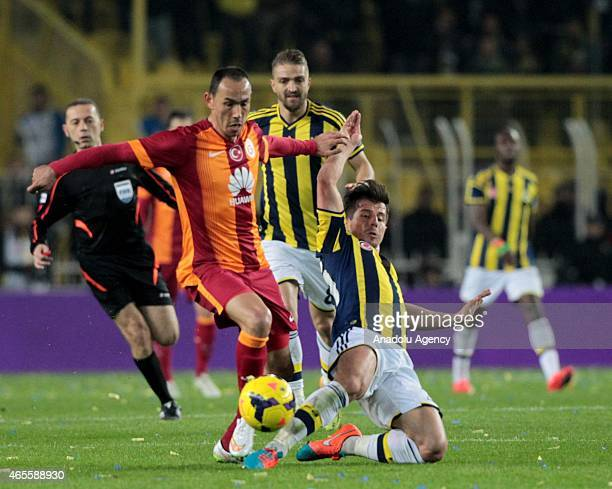 Emre Belozoglu of Fenerbahce in action against Umut Bulut of Galatasaray during the Turkish Spor Toto Super League derby game between Fenerbahce and...