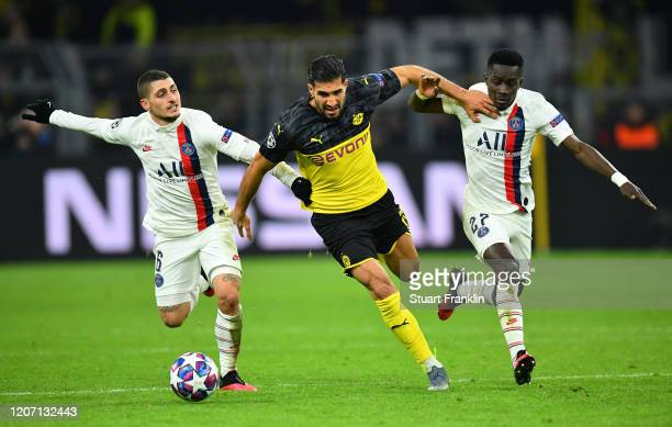 Emre Can of Borussia Dortmund is challenged by Marco Verratti and Idrissa Gueye of Paris SaintGermain during the UEFA Champions League round of 16...