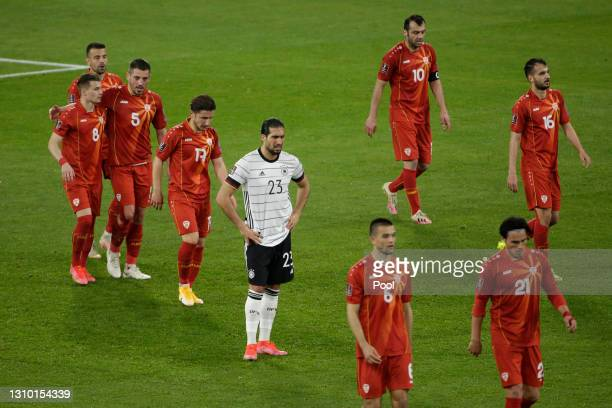 Emre Can of Germany looks dejected as Goran Pandev of North Macedonia celebrates scoring their team's first goal with teammates during the FIFA World...