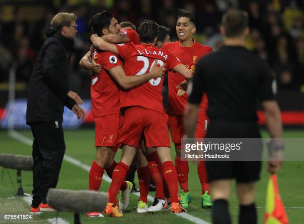 Emre Can of Liverpool is congratulated by teammates after scoring the opening goal during the Premier League match between Watford and Liverpool at...