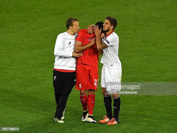 Emre Can of Liverpool is consoled by Daniel Carrico of Sevilla and Lucas Leiva of Liverpool after the UEFA Europa League Final match between...