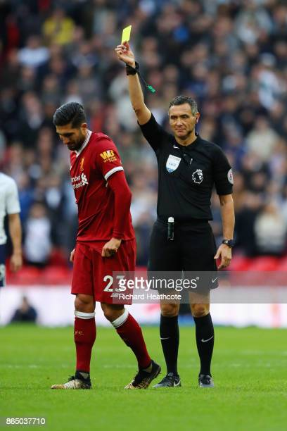 Emre Can of Liverpool is shown a yellow card by referee Andre Marriner during the Premier League match between Tottenham Hotspur and Liverpool at...