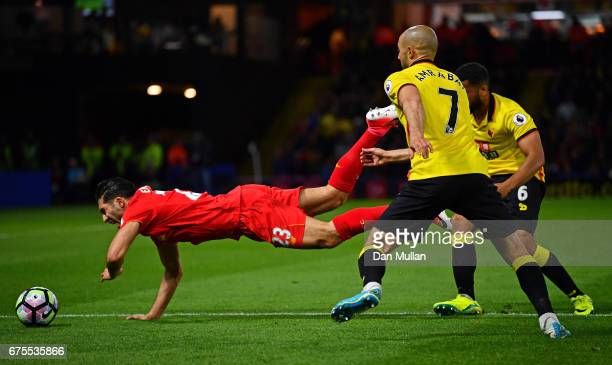 Emre Can of Liverpool isbrought down by Nordin Amrabat and Adrian Mariappa of Watford during the Premier League match between Watford and Liverpool...