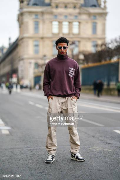 "Emre Celik aka ""Sweamyy1"" wears white sunglasses from Versace, a purple turtleneck pullover from Yves Ricci, beige cargo pants with side pockets from..."