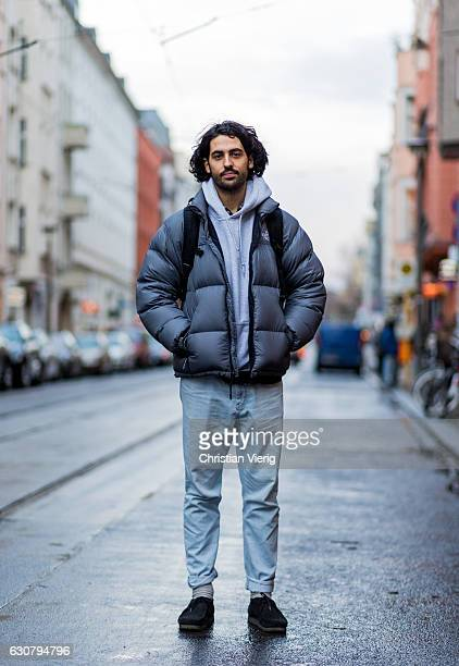 Emre wearing a grey down feather jacket grey hoody denim jeans and backpack on January 2 2017 in Berlin Germany