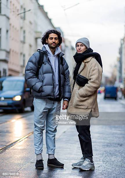 Emre wearing a grey down feather jacket grey hoody denim jeans and backpack and Judith wearing a beige teddy coat black belt bag grey scarf black...