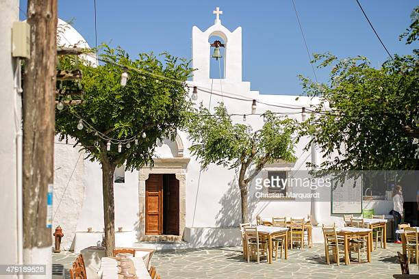 Emtpy white restaurant tabels in front of a old Greec orthodox church in a backstreet in the town of Ano Meria on June 13 2015 in Folegandros Greece...
