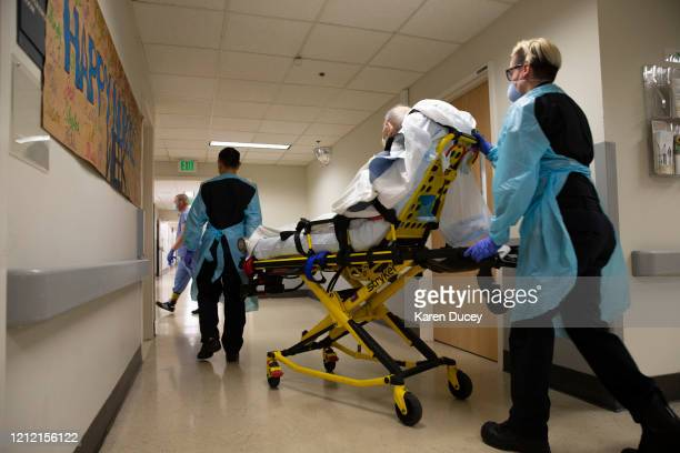 EMTs Daniel Kiga and Stephanee Richards transfer a patient out of the acute care COVID unit at Harborview Medical Center on May 7 2020 in Seattle...