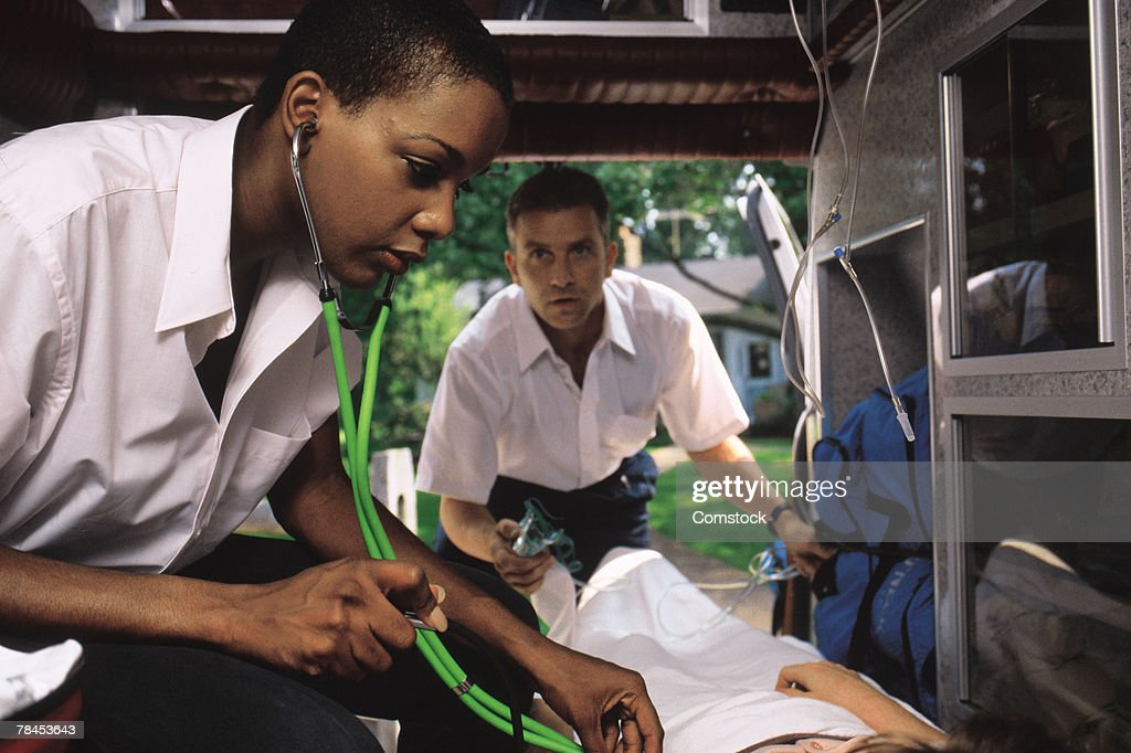 EMTs treating patient in ambulance : Stockfoto