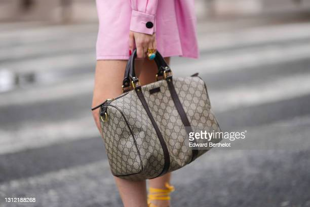 Emy Venturini @sustainably_by_emy , stylist, wears a pale pink vintage dress from Krizia, a brown monogram print large bag from Gucci, a blue and...