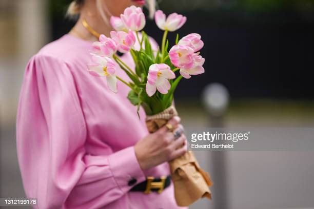 Emy Venturini @sustainably_by_emy , stylist, wears a pale pink vintage dress from Krizia, a Hermes belt, holds a bunch / bouquet of flowers, on April...