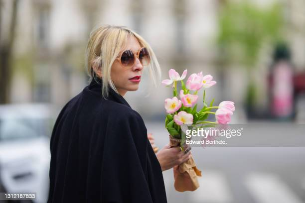 Emy Venturini @sustainably_by_emy , stylist, wears sunglasses from Komono, a black wool long coat, holds a bunch / bouquet of flowers, on April 11,...