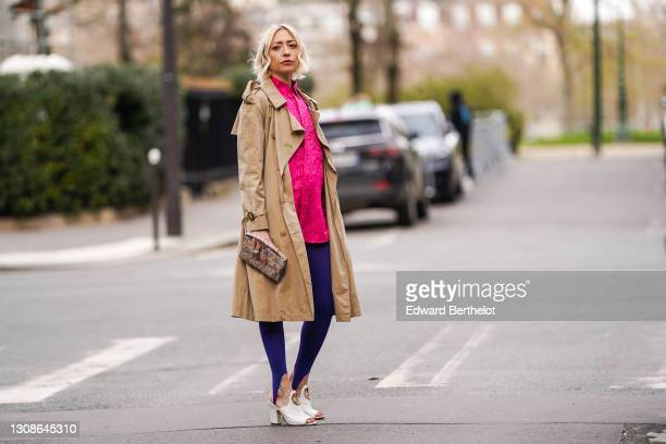 Emy Venturini @sustainably_by_emy wears a Burberry beige trench coat, a neon pink long shiny shirt with floral pattern from Dress to Drama, a clutch...