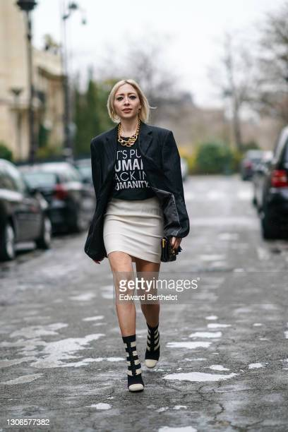 Emy Venturini wears a golden necklace, a black oversize blazer jacket, a black t-shirt with a printed slogan from Kindom, a white short skirt, a...