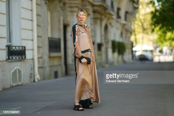 Emy Venturini wears gold Prada sunglasses, gold earrings, a brown with black spots ruffled long Sacai dress with a black belt and matching scarf, a...