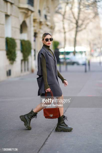 Emy Venturini wears sunglasses from Linda Farrow, earrings, a gray oversized sleeveless long jacket worn as a dress from FSTD, a green khaki...