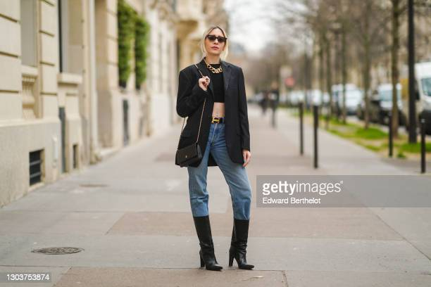 Emy Venturini wears sunglasses, golden earrings, a golden large chain necklace, a black cropped top from Elisabetta Franchi, a black oversized blazer...