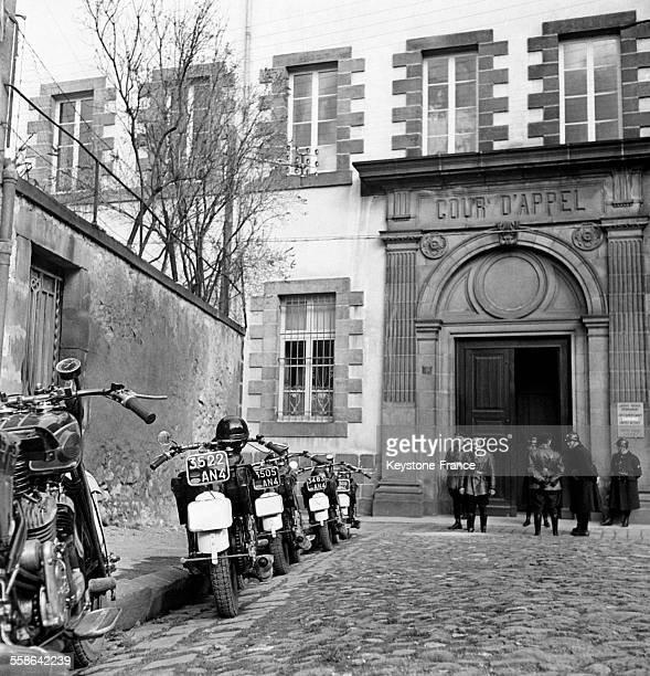 En attendant la sortie des inculpés les gardes motocyclistes qui escortent les voitures attendent de repartir à Riom France en 1942