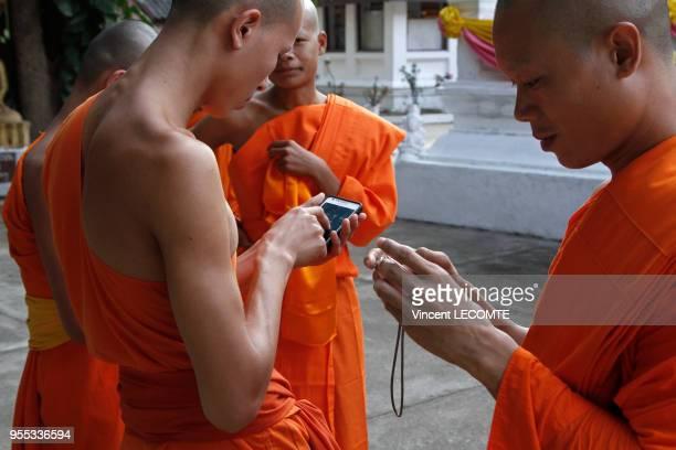 En attendant le début de la cérémonie de la prière du soir des moines bouddhistes asiatiques en tenue traditionnelle comparent leurs photographies...