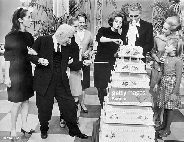 Charlie Chaplin is about to stab his sixtiered birthday cake during a surprise party thrown for him on the set of A Countess from Hong Kong the film...