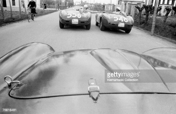 En Route to The Mille Miglia April 1956 On the road from Maranello to Brescia Luigi Musso gives Eugenio Castellotti a cigarette as the car of Peter...
