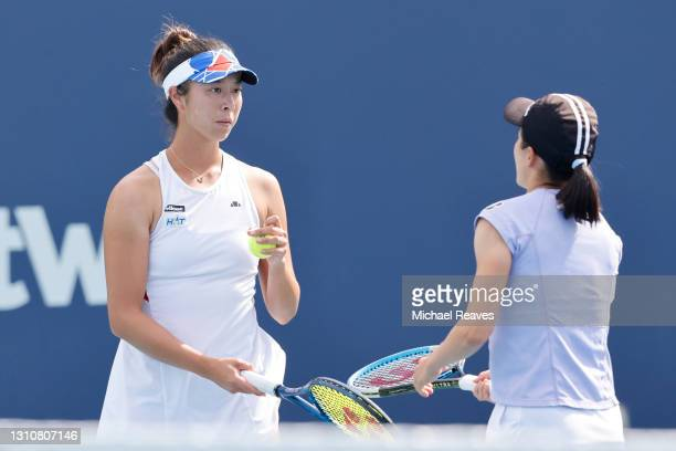 Ena Shibahara and Shuko Aoyama of Japan confer against Hayley Carter of the United States and Luisa Stefani of Brazil during the final of the Miami...