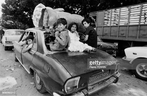 Enafants sortant de la lunette arrière d'un ePeugeot 504 dans une rue de Beyrouth le 10 aout 1982 Liban