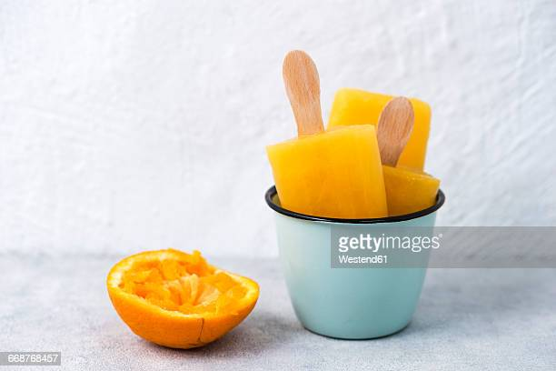 Enamel cup of homemade orange popsicles and a squeezed orange peel