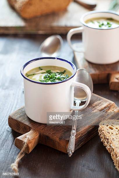 Enamel cup of pea soup with chives