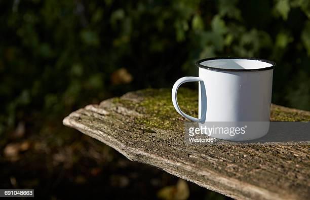 Enamel mug on wooden bench
