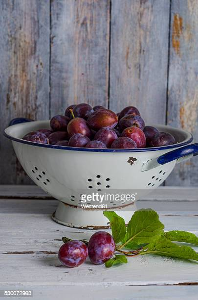 Enameled colander of plums on wooden table