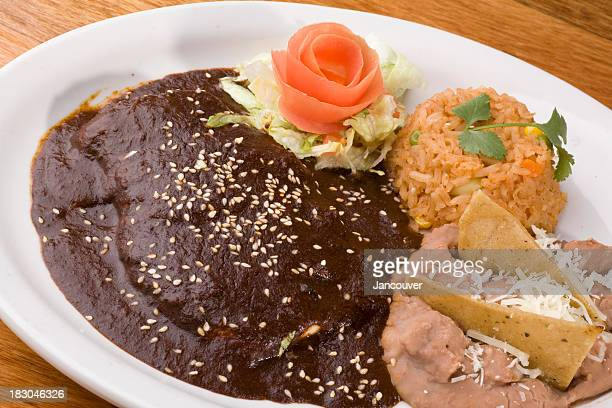 Enchiladas served with rice and beans